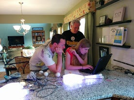 Lauren, Charles, and her dad around the laptop