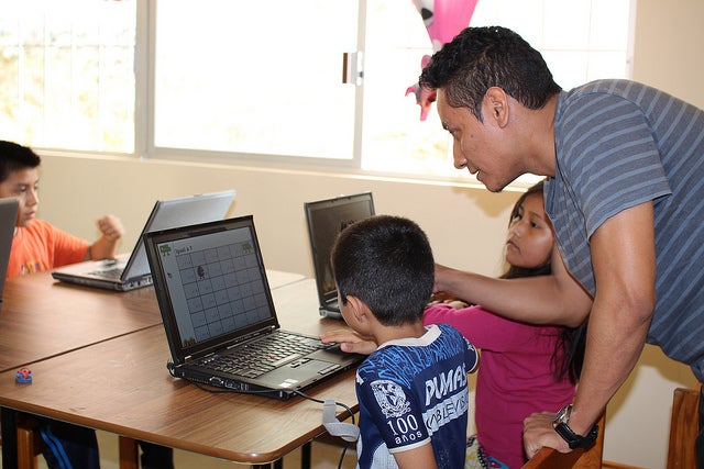 A teacher instructing a student on a donated laptop.