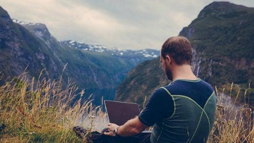 Man at laptop on a mountain
