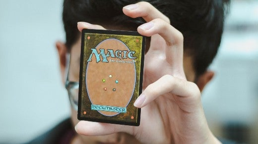 Holding a Magic the Gathering deckmaster card