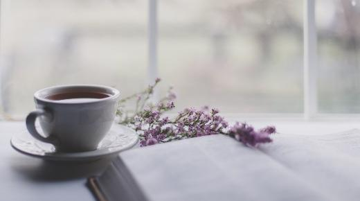 Ceramic mug of tea or coffee with flowers and a book in front of a window