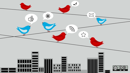 Red and blue birds chatting on telephone wire over city skyline