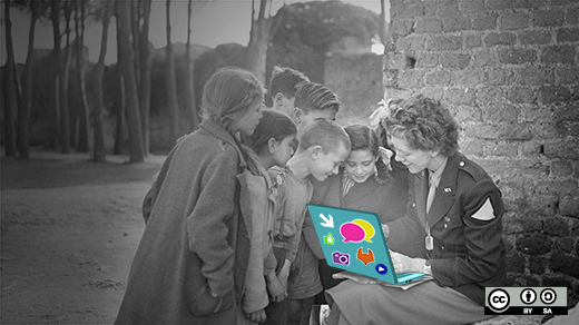 Group of kids crowded around a teacher with a laptop