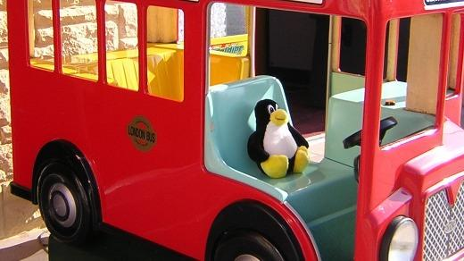 tux the penguin driving a toy bus