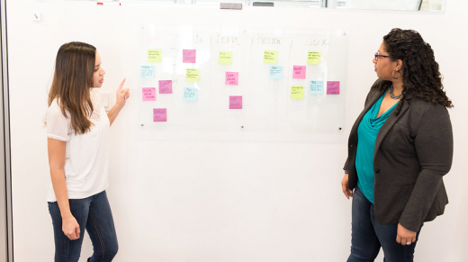two women kanban brainstorming and brainmapping with post-it notes on a whiteboard