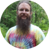 Tie dye wearing hippie Matthew with a long beard hiking in the woods.