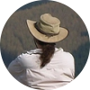 Rear view of a person with a ponytail wearing a wide-brim canvas hat