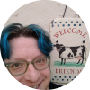 "Blue-haired Eric next to a slate shingle with a cow and the word ""welcome"" painted upon it."