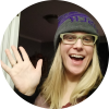 "A blonde woman who is waving as though saying ""Hi!"", wearing a gray and purple snow hat and beige glasses"