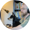 bearded bespectacled guy and small dog seated & looking at a computer