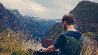 Man at laptop on a mountain