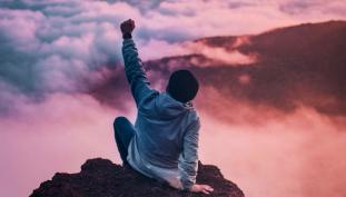 Person on top of a mountain, arm raise