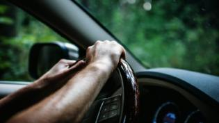 Driver's hands on the steering wheel of a car