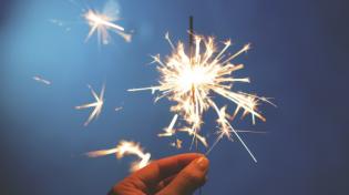 hand holding lit sparkler