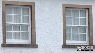 2 windows with brown frames on a white exterior wall