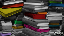 Stack of books in black and white with a few colored ones
