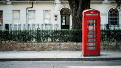 Red telephone booth on a street in England