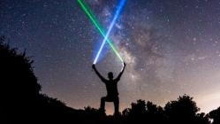 Man with lasers in night sky