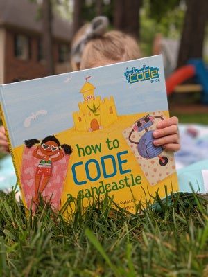 Young girl reading How to Code a Sandcastle