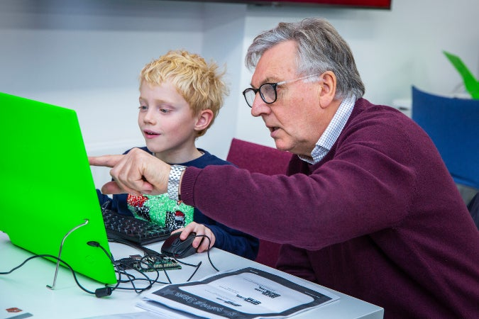 Older adult and child working together at Raspberry Jam